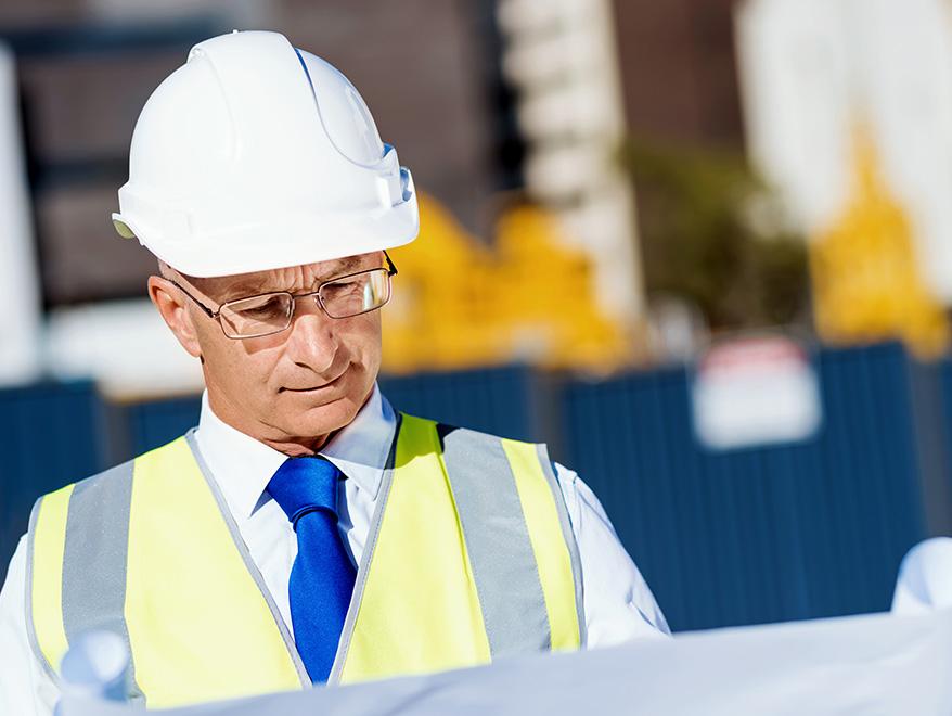 Man looking at blue prints in white hardhat | SAE Inc.