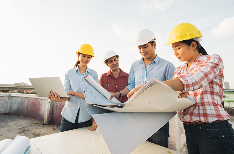 Four people looking at blue prints wearing hardhats | SAE Inc.