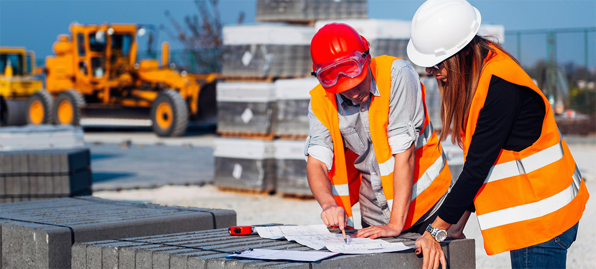 Two people working in orange vests and hardhats | SAE Inc.